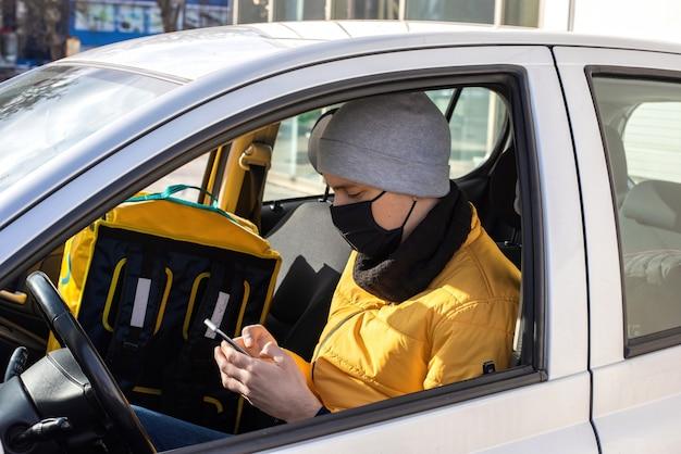 Un Homme Dans La Voiture Avec Un Masque Médical Noir Est Sur Son Téléphone, Sac à Dos Sur Le Siège Photo gratuit