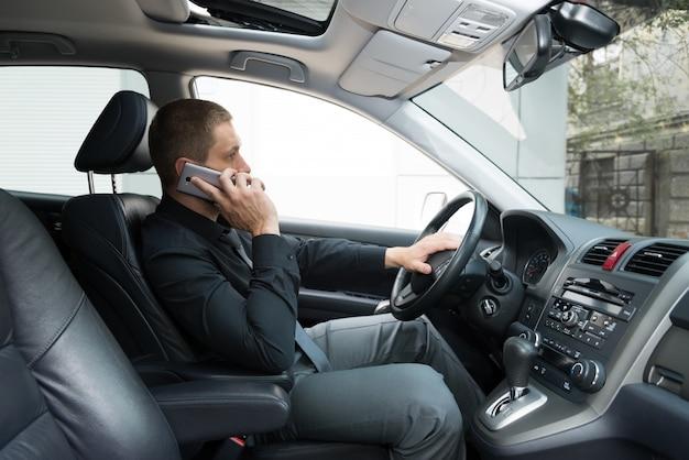 L'homme Dans La Voiture Parle Au Téléphone Photo Premium