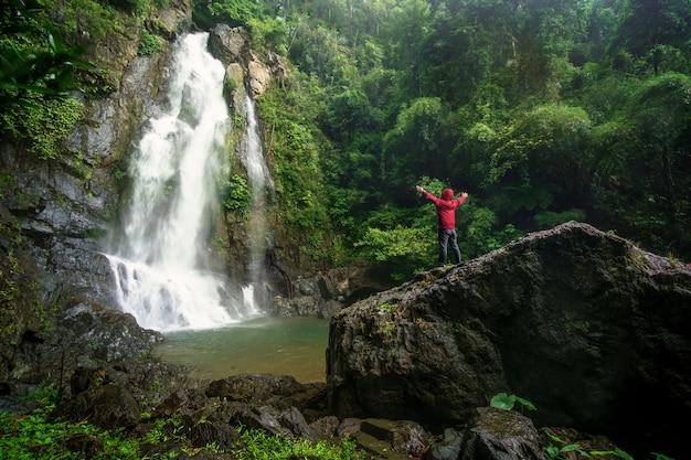Un homme debout au concept de voyage cascade Photo Premium