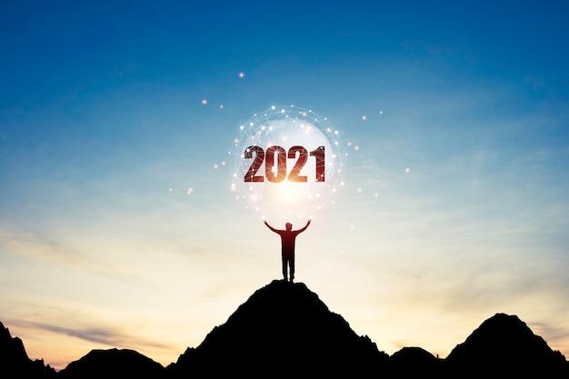 Un Homme Debout Au Sommet De La Montagne Et Lève Les Deux Mains Pour Porter Le Monde Avec Connexion Et Numéro 2021 Sur Ciel Bleu. C'est Le Symbole Du Début Et De La Bonne Année 2021. Photo Premium