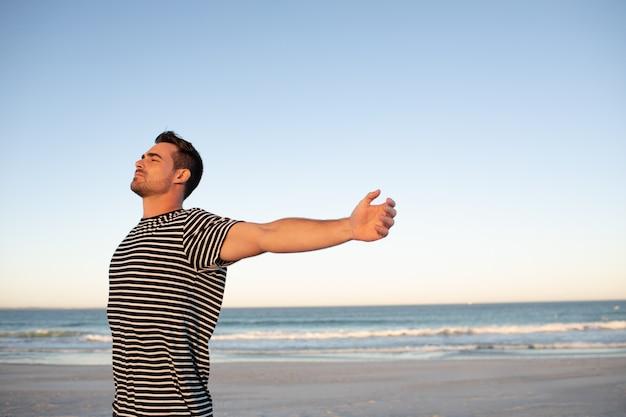 Homme debout avec les bras tendus sur la plage Photo gratuit