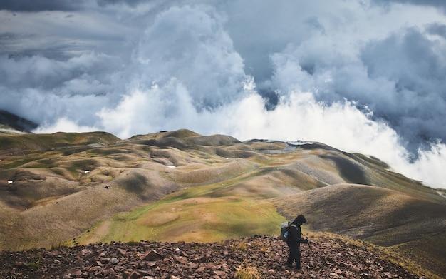 Homme Debout Sur Une Colline Couverte De Verdure Sous Un Ciel Orageux Pendant La Journée Photo gratuit