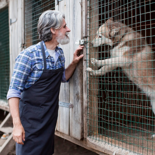 Homme Debout à Côté De La Cage De Chien Photo gratuit