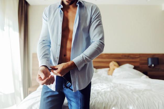 Homme Debout à Côté D'un Lit Dans Une Chambre D'hôtel Et Boutonner Une Chemise. Photo Premium
