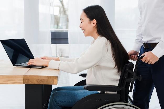 Homme debout derrière la femme handicapée souriante assise sur un fauteuil roulant à l'aide d'un ordinateur portable Photo gratuit