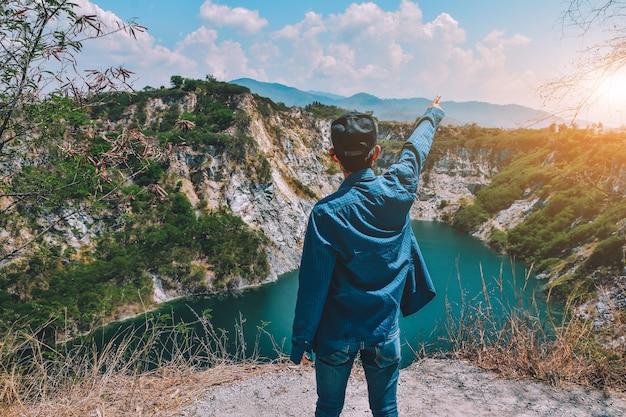 Homme debout sur la montagne rocheuse à la vue du lac Photo Premium