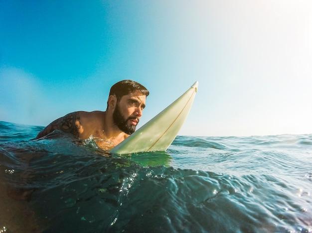 Homme debout avec planche de surf dans l'eau bleue Photo gratuit