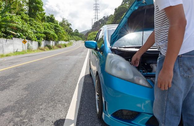 Homme debout sur la route avec une voiture défectueuse au milieu de la route Photo Premium
