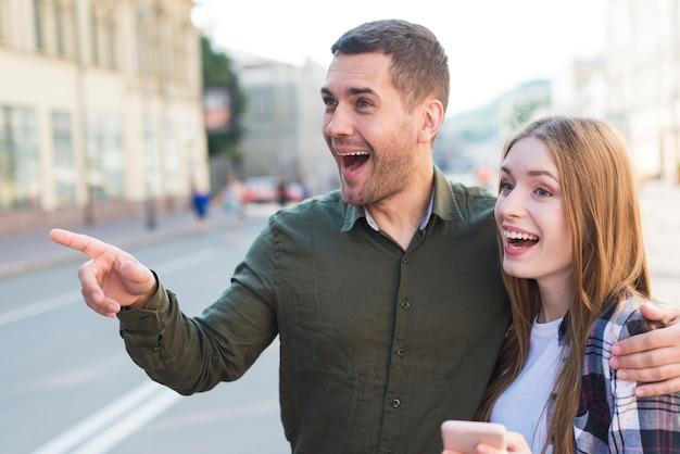 Homme debout avec sa petite amie montrant quelque chose dans la rue Photo gratuit