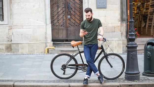 Homme debout avec son vélo à l'aide d'un smartphone Photo gratuit