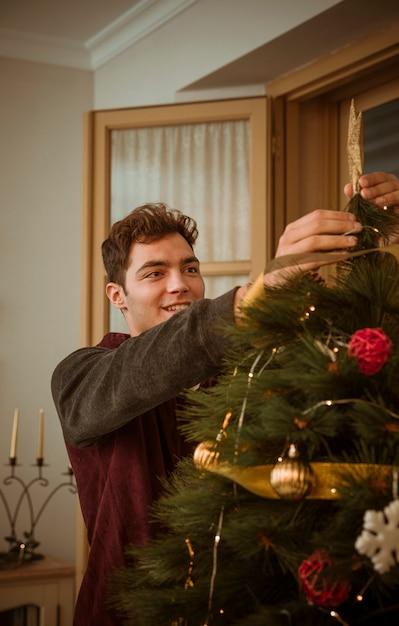 Homme décorer un arbre de noël avec étoile Photo gratuit