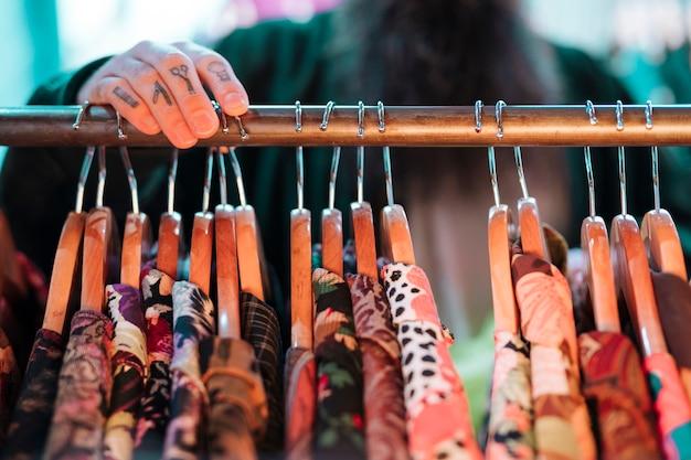 Homme défocalisé choisissant une chemise suspendue au rail dans la boutique Photo gratuit