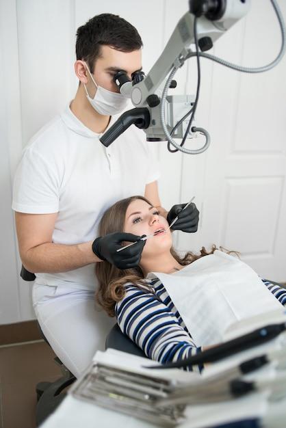 Homme Dentiste Avec Des Outils Dentaires - Microscope, Miroir Et Sonde Traitant Les Dents Des Patients Au Bureau De La Clinique Dentaire Photo Premium