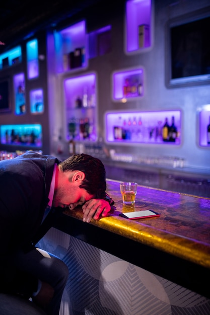 Homme Déprimé Ayant Du Whisky Au Comptoir Du Bar Photo Premium