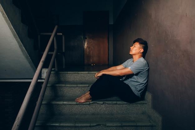 Homme déprimé. un homme assis dans l'escalier du bâtiment Photo Premium