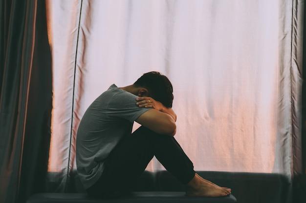 Homme déprimé. un homme assis, étreignant ses genoux sur la chaise, près de la fenêtre. Photo Premium