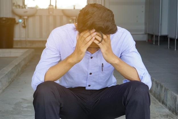 Homme déprimé tenant le front à deux mains, assis sur l'échelle des toilettes Photo Premium