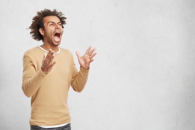 Un Homme Désespéré Fou Fou Hurle De Panique, Fait Des Gestes Avec Les Mains Photo gratuit