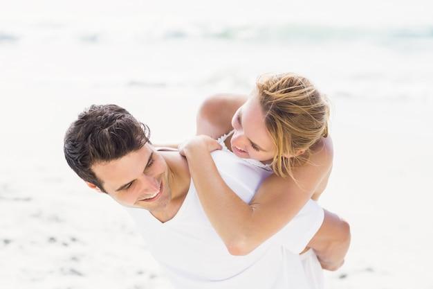 Homme donnant un piggy à la femme sur la plage Photo Premium
