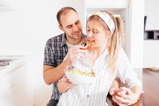Homme donnant de la salade à sa femme dans la cuisine Photo gratuit