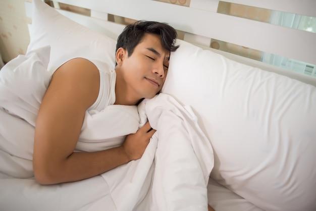Homme dormant sur le lit le matin Photo gratuit