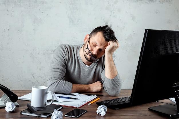Homme dormant à une table dans le bureau. le concept de travail de bureau, beaucoup de travail, fatigue, paresse. espace de copie. Photo Premium