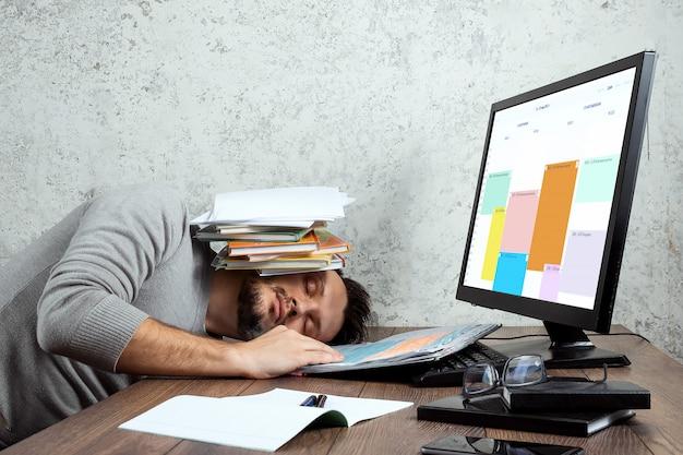 Homme dormant à une table dans le bureau avec les documents sur sa tête. Photo Premium