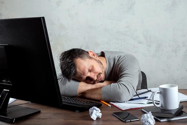 Homme dormant à une table dans le bureau. Photo Premium