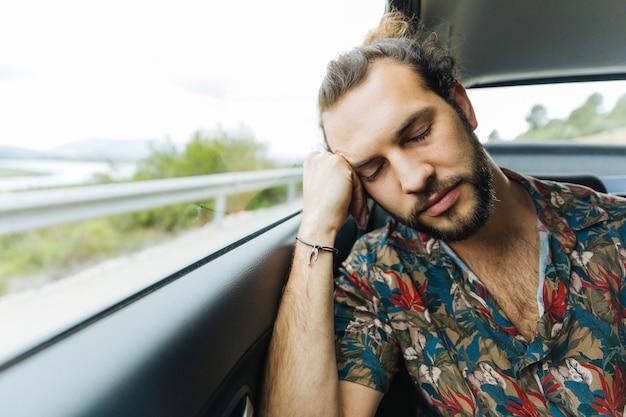 Homme dort dans voiture Photo gratuit