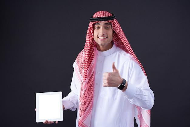 Homme du moyen-orient posant avec tablette blanche isolée. Photo Premium