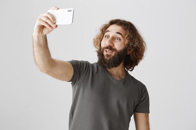 Homme Du Moyen-orient Souriant Enthousiaste Prenant Selfie Avec Smartphone Photo gratuit