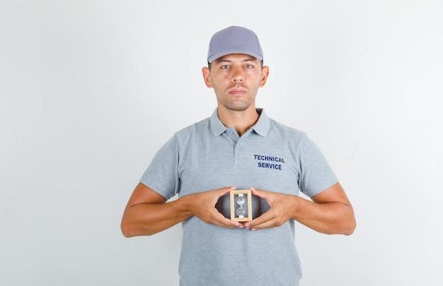 Homme Du Service Technique En T-shirt Gris Avec Capuchon Tenant Le Sablier Et à La Ponctualité Photo gratuit
