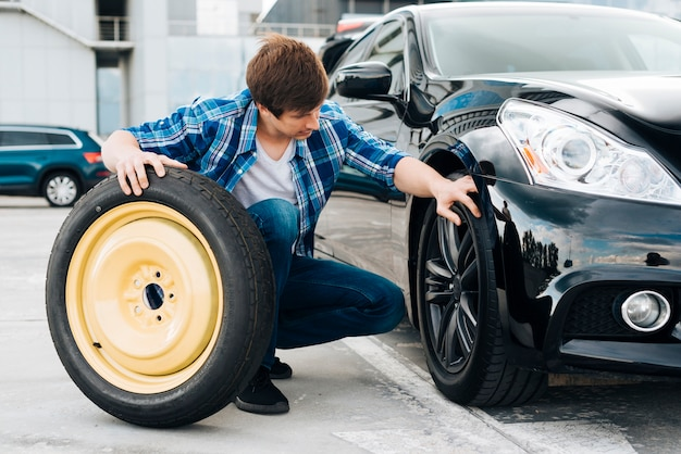 Homme échangeant un pneu de voiture avec une roue de secours Photo gratuit