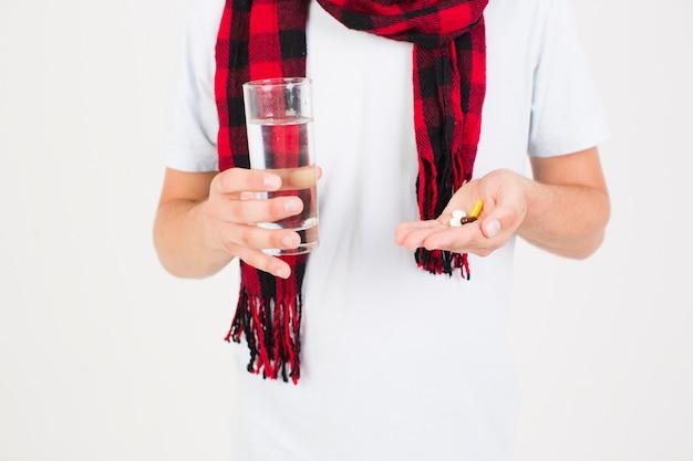 Homme en écharpe avec des pilules à la main Photo gratuit
