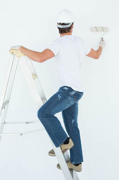 Homme, sur, échelle, peinture, à, rouleau Photo Premium