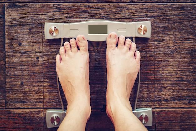 Homme sur une échelle de poids sur plancher en bois, concept de régime. Photo Premium
