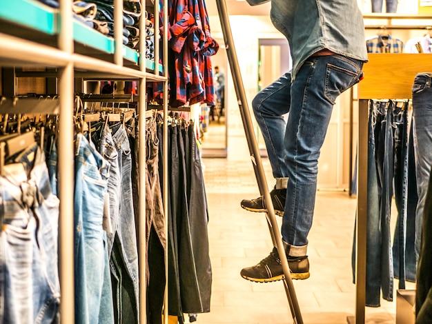 Homme sur l'échelle en train de ramasser un jean sur l'étagère du magasin de vêtements Photo Premium