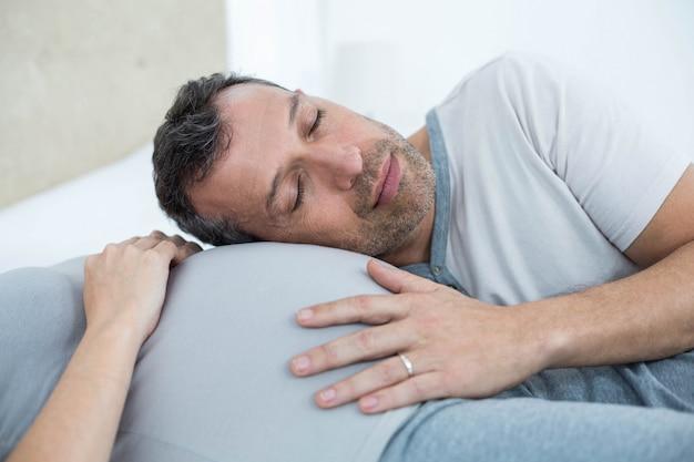 Homme écoutant le ventre d'une femme enceinte dans sa chambre Photo Premium