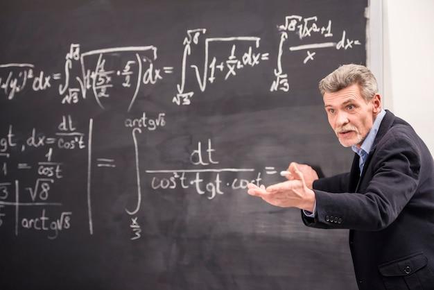 Un homme écrit une formule et lui demande de l'expliquer. Photo Premium