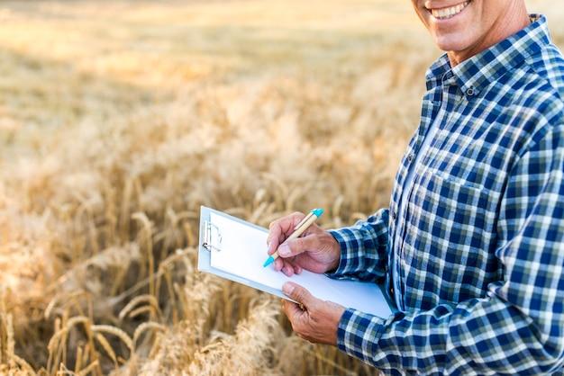Homme écrivant sur un presse-papiers dans un champ de blé Photo gratuit