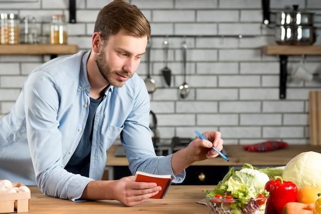 Homme écrivant recette ou plante diététique sur son journal intime en spirale Photo gratuit