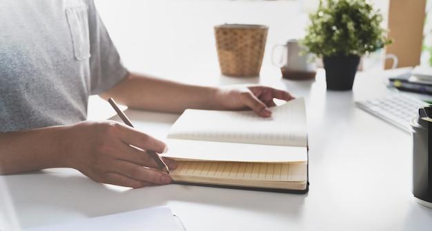 Homme écrivant ses idées sur cahier Photo Premium