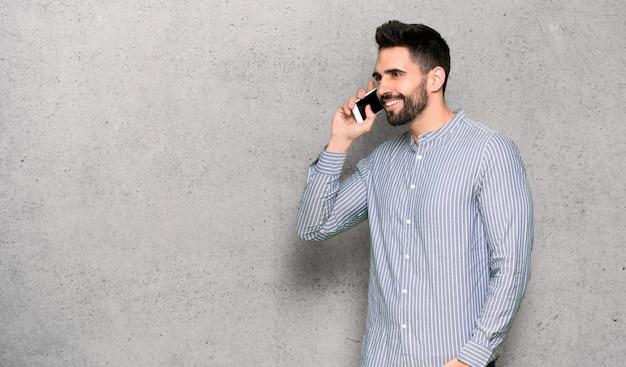 Homme élégant avec une chemise en gardant une conversation avec le téléphone portable sur un mur texturé Photo Premium