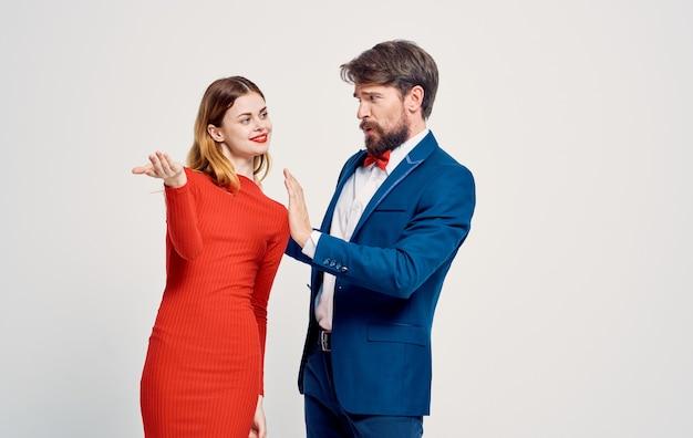 Un Homme élégant En Costume Et Une Femme En Robe Rouge Sur Une Publicité Légère. Photo Premium