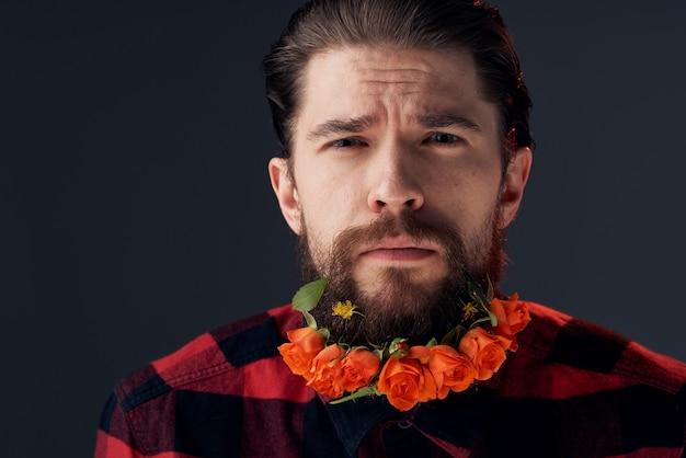 Un Homme élégant Dans Une Chemise à Carreaux Fleurs Dans Une Barbe Close-up Fond Sombre. Photo De Haute Qualité Photo Premium
