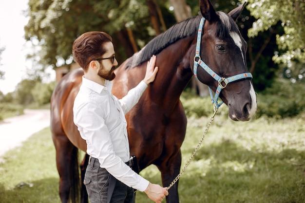 Homme élégant, debout à côté d'un cheval dans un ranch Photo gratuit