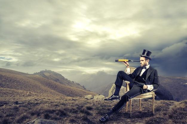 Homme élégant découvrant la nature avec une portée. Photo Premium