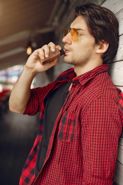 Homme élégant et élégant dans une ville avec vape Photo gratuit