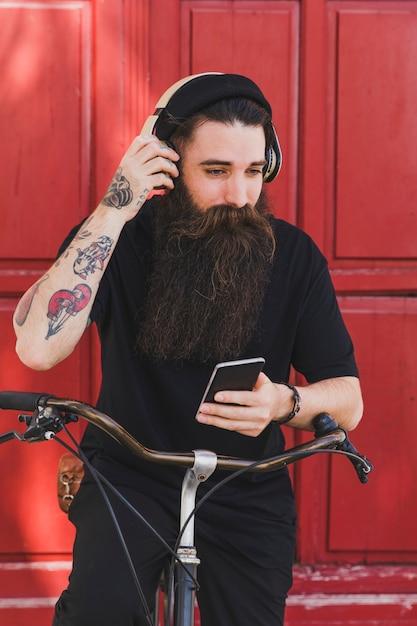 Homme élégant jeune cycliste écoutant de la musique au casque contre une porte en bois Photo gratuit