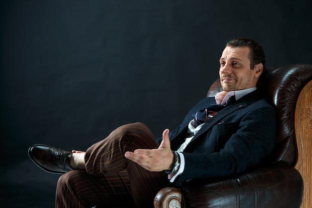 L'homme élégant Mature Dans Un Costume Sur Un Studio Gris. Homme Affaires, Séance, Sur, A, Fauteuil Photo gratuit